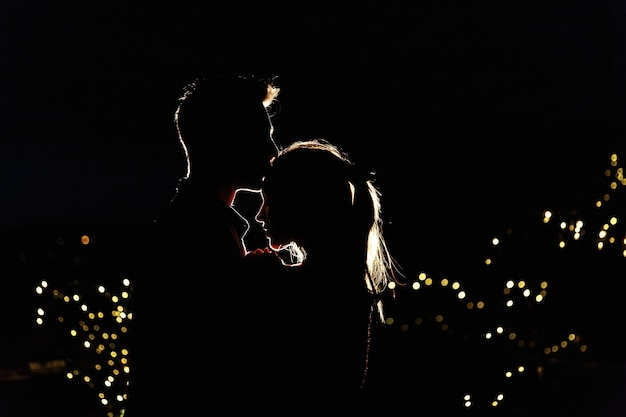 Silhouettes of a lovely young couple standing on the rooftop in the night Free Photo