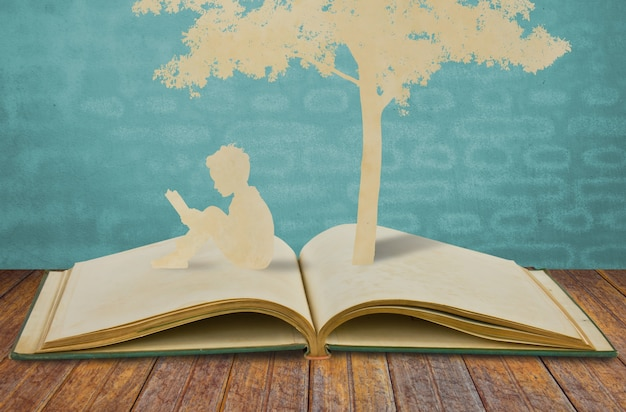 Silhouettes of a tree and a man on a book Free Photo