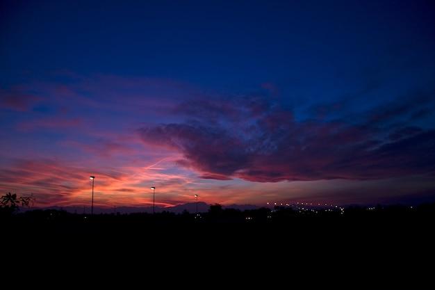 美しい夕日の曇り空の下で丘と街灯のシルエット 無料写真