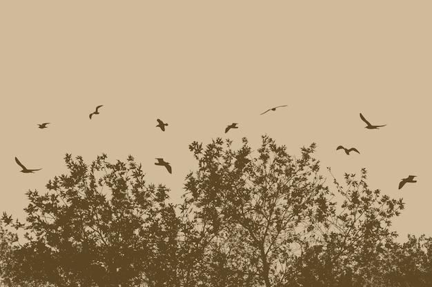 베이지 색 배경에 새를 비행 나무와 가지의 실루엣 무료 사진