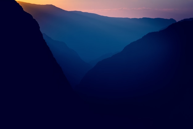 Silhouettes and outlines of a mountain massif in the setting sun Premium Photo
