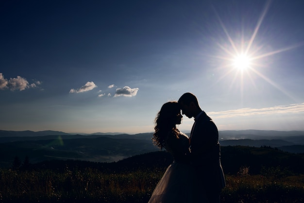 Silhouettes of wedding couple standing in the rays of sun before mountain landscape Free Photo