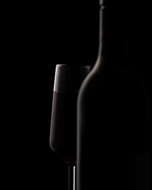 Silhouettes of wine bottle and wine glass on black Free Photo