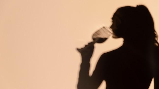 Sagome di donna che beve vino Foto Gratuite