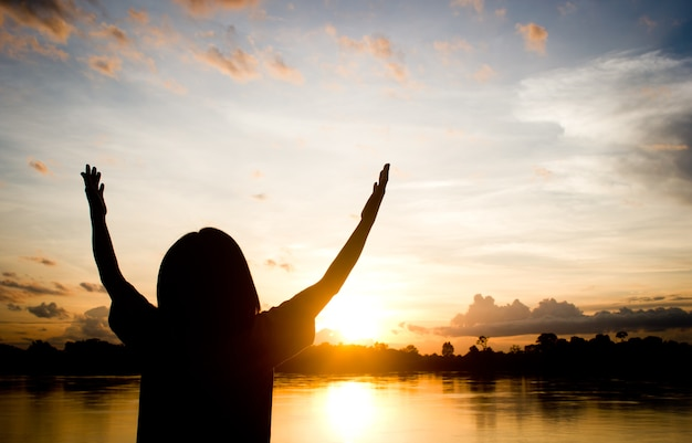 Silhouettes women praying hand over beautiful sun set background. Premium Photo