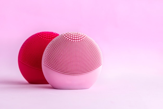 Silicone facial cleansing brushes with cleansing brush for massaging skin care on pink background. Premium Photo