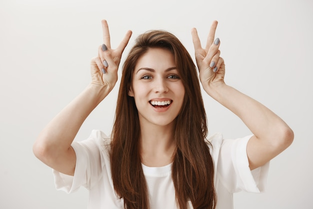 Silly adorable girl showing quotation marks gesture and smiling happy Free Photo