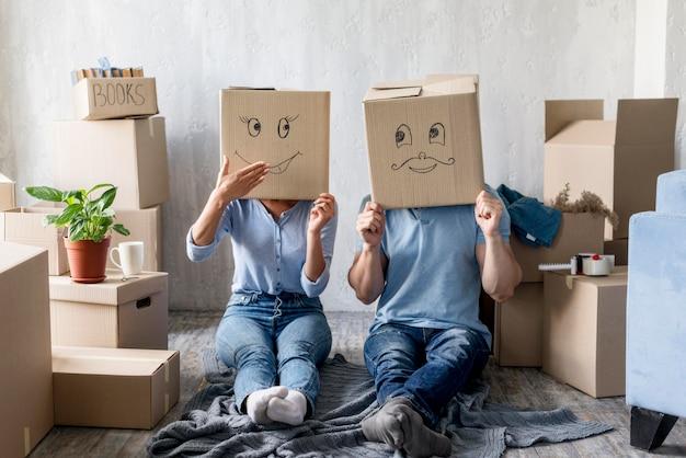 Глупая пара дома в день переезда с коробками над головой Бесплатные Фотографии