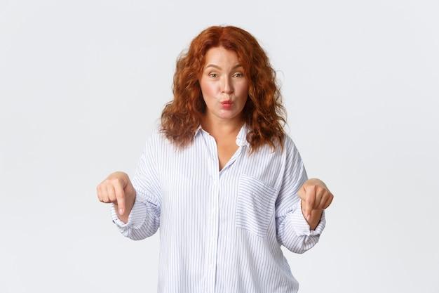Sciocca e carina donna rossa di mezza età che fa il broncio e dà un suggerimento puntando il dito verso il basso, mostrando un banner con un'offerta speciale, facendo un annuncio, in piedi su sfondo bianco. Foto Gratuite