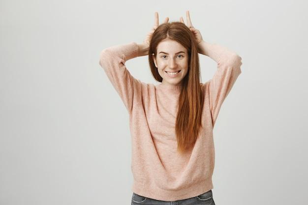 頭の上に角を見せて笑顔の愚かなかわいい赤毛の女の子 無料写真