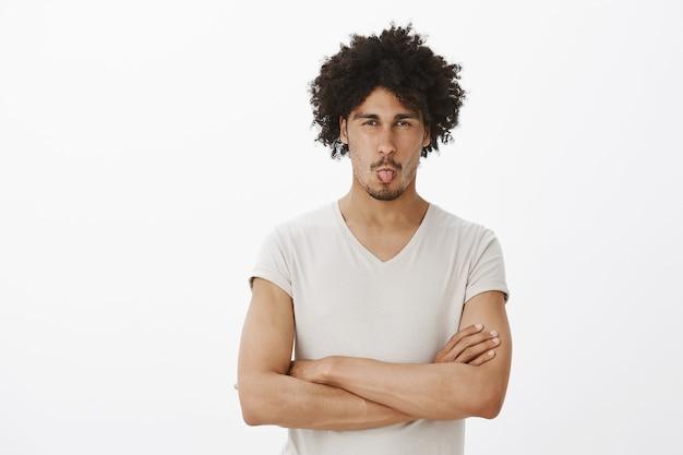 Глупый темнокожий мужчина гримасничает и показывает язык от отвращения Бесплатные Фотографии