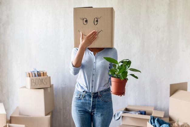 Donna sciocca in posa con scatola sopra la testa e pianta in mano durante l'imballaggio per muoversi Foto Gratuite