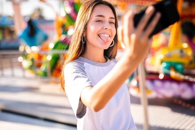 Silly woman taking selfie with phone Free Photo