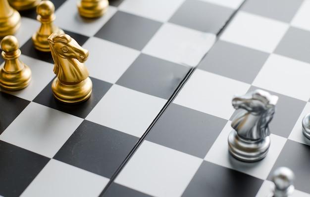 Серебряный и золотой рыцарь на шахматной доске. шахматные рыцари голова к голове. Premium Фотографии