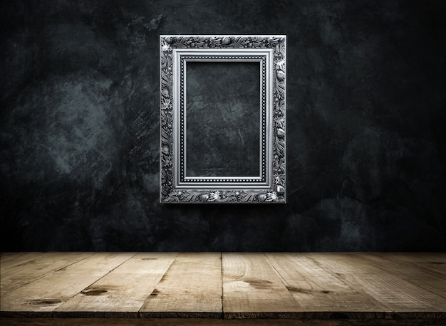 Silver antique photo frame on dark grunge wall background with wooden table top Premium Photo