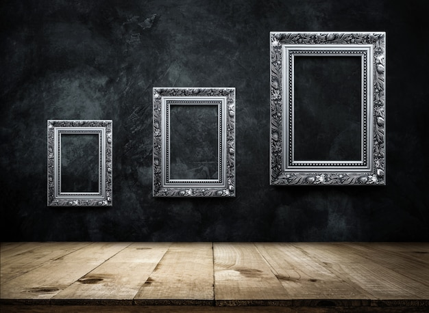 Silver antique picture frame on dark grunge wall with wooden table top Premium Photo