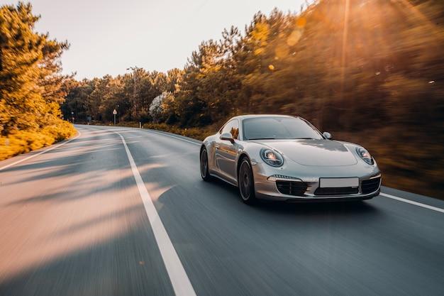 도로에서 은색 미니 쿠페. 햇빛 아래에서 운전하십시오. 무료 사진
