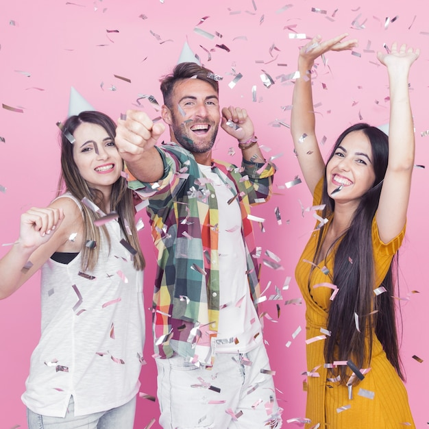Silver confetti falling over the friends dancing against pink background Free Photo
