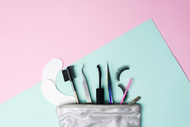Silver cosmetic bag with a set for eyelash extension and dyeing. eyelash extension tweezers, false eyelashes, eye patches and eyebrow brush Premium Photo