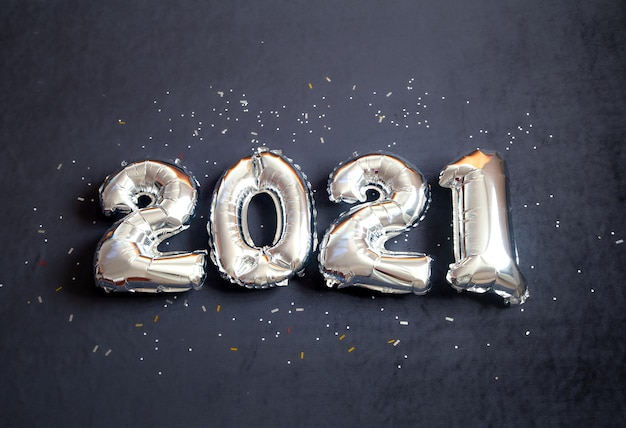 Silver foil balloons made new years number on black background. Free Photo