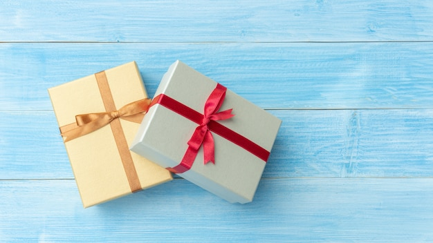 Silver and gold gift box on a blue wooden table. Premium Photo