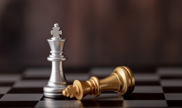 Silver king standing and gold falling on chess board Premium Photo
