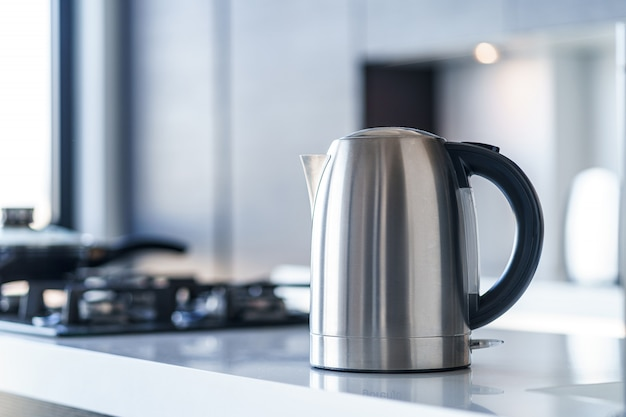 Silver metal electric kettle for boiling water and making tea on a table in the kitchen interior. household kitchen appliances for makes hot drinks Premium Photo
