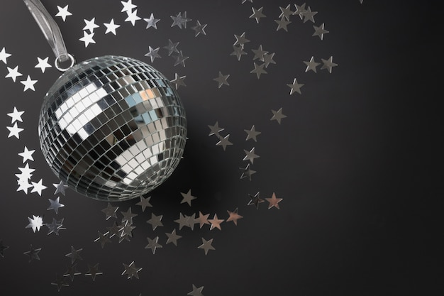 Silver mirror disco ball glitter with stars on black background. festive holiday concept. Premium Photo