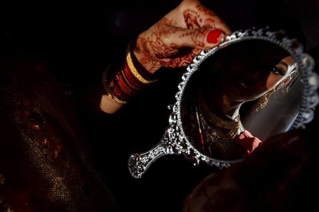 Silver mirror in hands of hindu bride with henna tattoos Free Photo