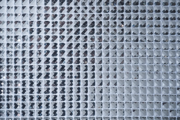 Silver mosaic pattern of tiles.wall is decorated with stained glass small plate ,beautiful mosaic wall or ceramic wall for pattern background Premium Photo