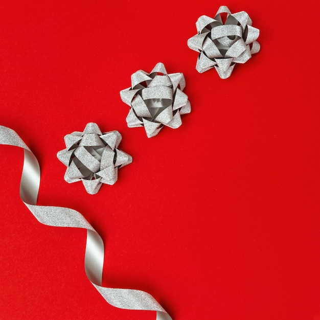 Silver paper ribbon tie on red background with copy space, christmas gift packaging decoration. Premium Photo