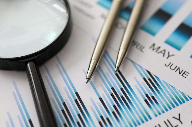 Серебряные ручки лежат на красочных статистических документах с крупным планом увеличительного стекла Premium Фотографии