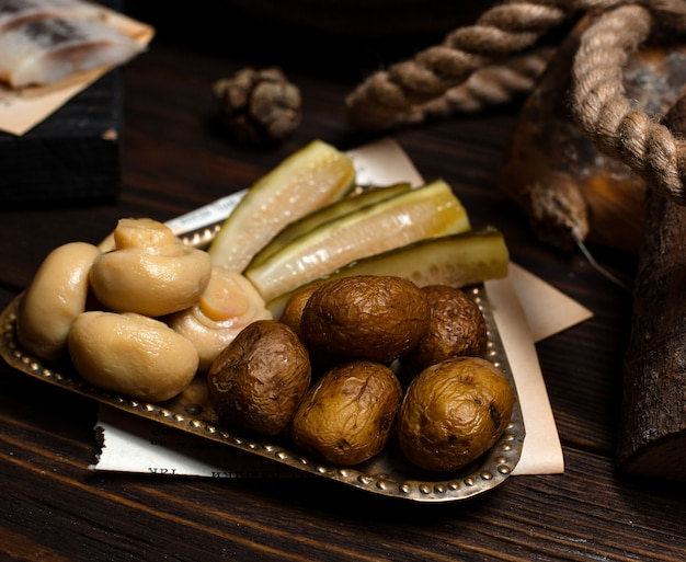 Silver plate of pickled mushrooms, cucumbers and baked potatoes Free Photo
