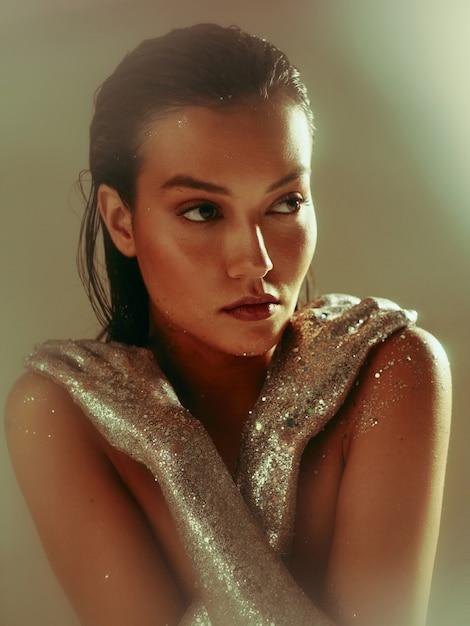 Серебряный сверкающий боди-арт, молодая девушка с мокрыми волосами и праздничным идеальным макияжем позирует в студии Premium Фотографии