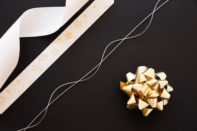 Silver string; white and star shape ribbon and golden bow on black background Free Photo