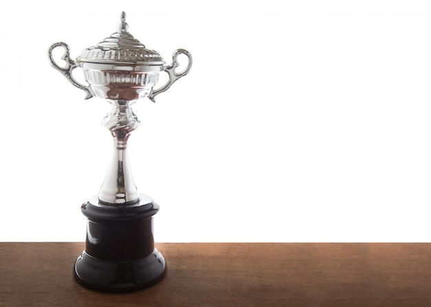 Silver trophy on wooden table isolated over white background. Premium Photo