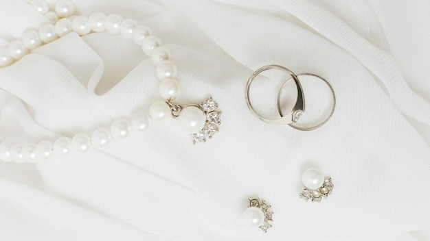 Silver wedding rings; earrings and pearl necklace on white lace Premium Photo