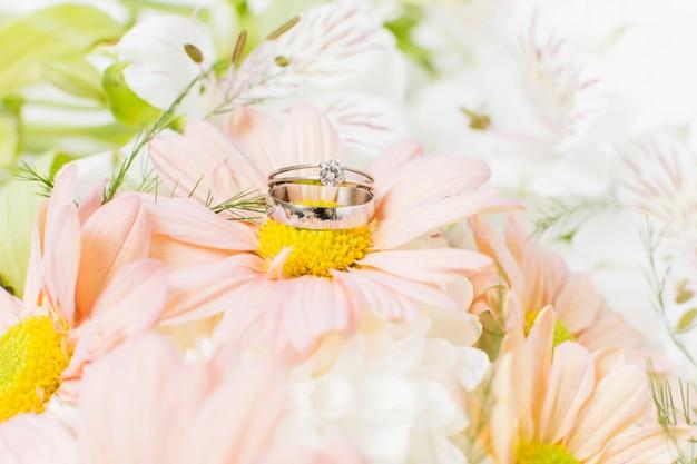 Silver wedding rings on pink gerbera flower bouquet Free Photo