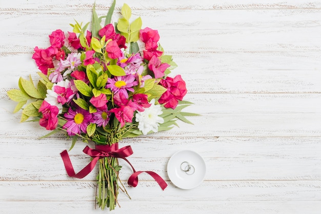 Silver wedding rings on white plate near the colorful bouquet on wooden backdrop Free Photo