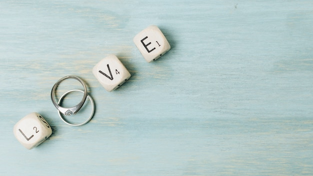 Silver wedding rings with love letters on wooden desk Free Photo