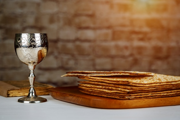 Silver wine cup with matzah, jewish symbols for the passover pesach holiday. passover concept. Premium Photo