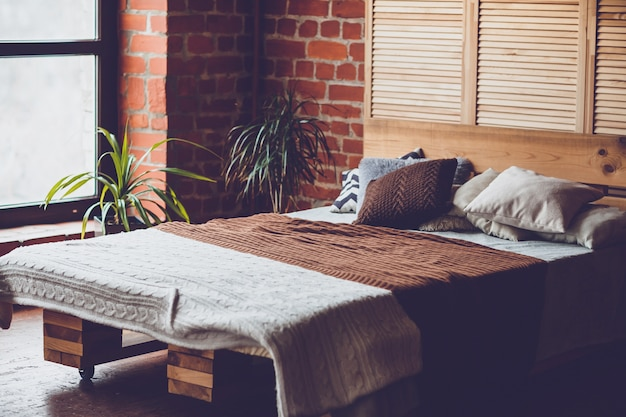 Simple bedroom with double bed, red brick wall and big window Premium Photo