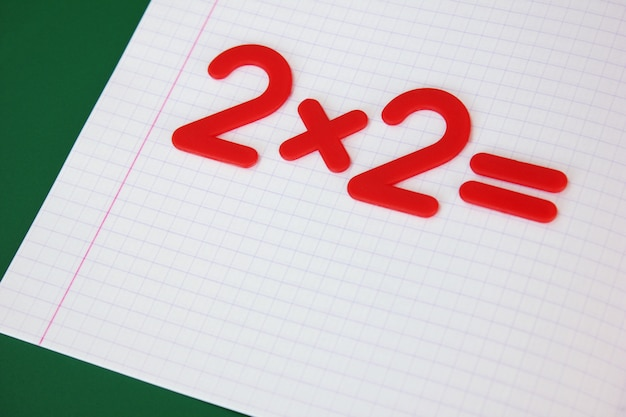 A simple mathematical example in a clean school notebook. back to school. Premium Photo
