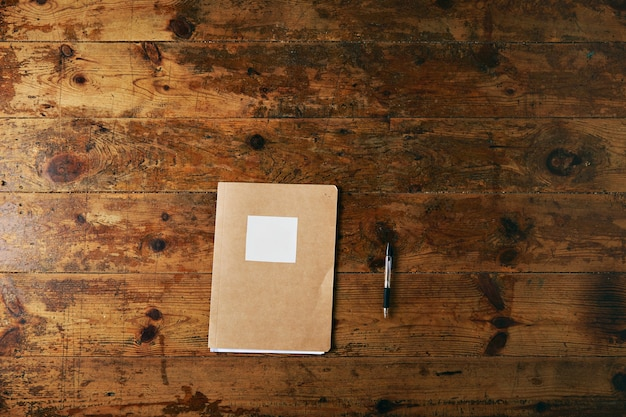 Simple notebook with craft paper cover and empty white label and a black ballpoint pen on a aged brushed wooden table Free Photo