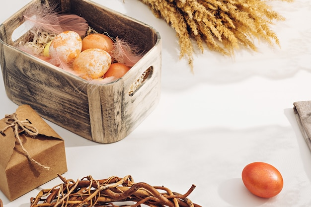 A simple rural composition. painted in pastel warm colors easter eggs in a wooden box in sunlight on a white table near the window Premium Photo
