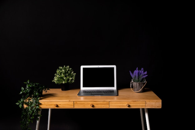 Simple wooden desk with gray laptop Free Photo