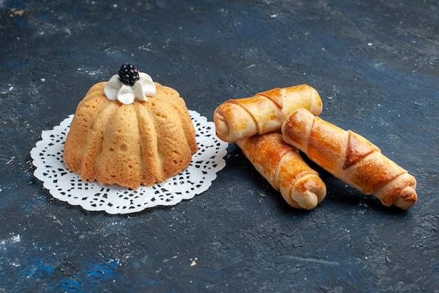 暗い机の上に腕輪と一緒にクリームとブラックベリーのシンプルなおいしいケーキ 無料写真