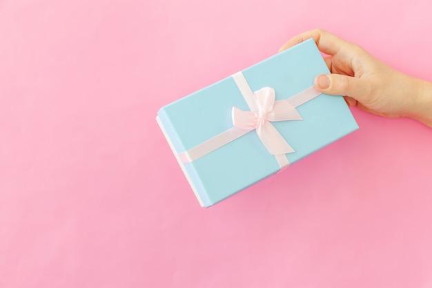 ピンクのテーブルで隔離の青いギフトボックスを持っている女性の女性の手をシンプルにデザイン Premium写真