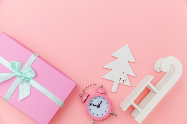 Simply minimal composition winter objects ornament sled fir tree ball gift box isolated pink pastel background Premium Photo