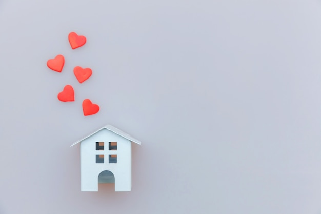 Simply minimal design with miniature white toy house with red heart isolated on white Premium Photo